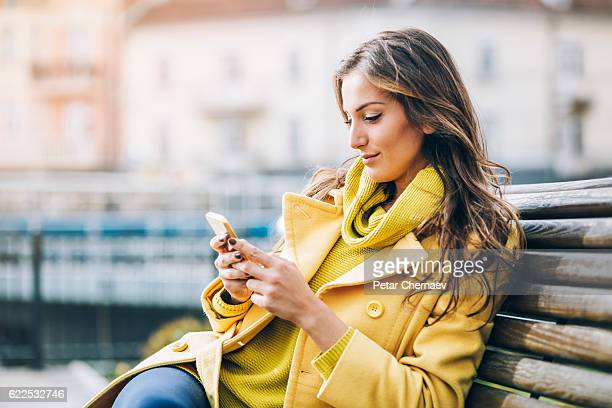 Beautiful woman texting on a bench