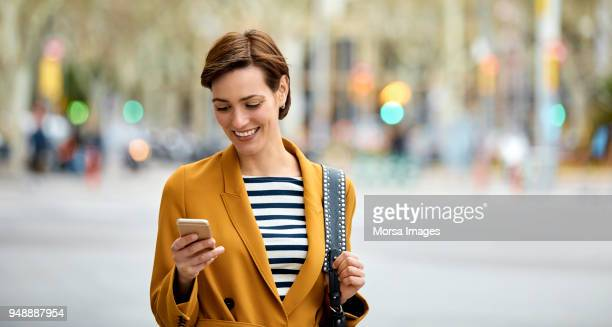 Beautiful woman texting on smart phone in city
