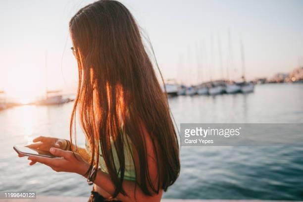 beautiful woman texting on street at sunset - cabello largo fotografías e imágenes de stock
