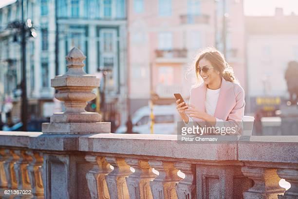 Beautiful woman texting on the bridge