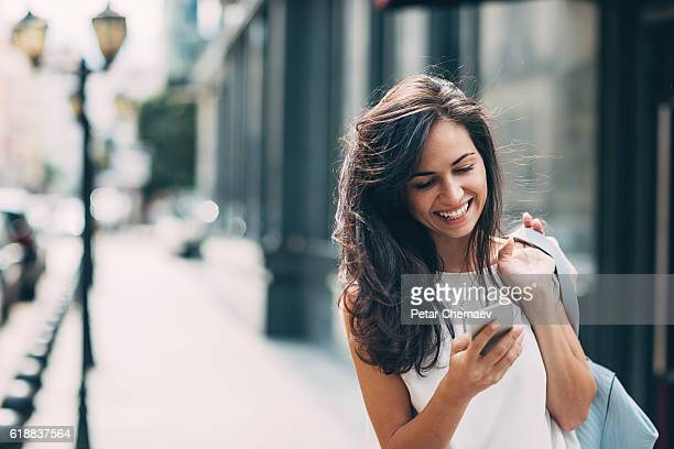beautiful woman texting on the street - mobiles gerät stock-fotos und bilder