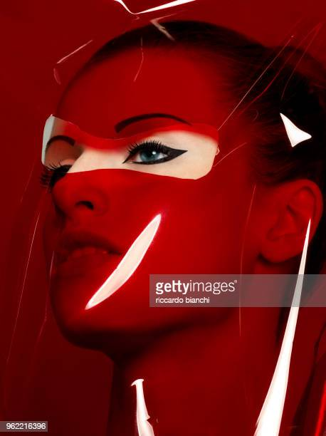 beautiful woman through red plastic with perfect black eyeliner