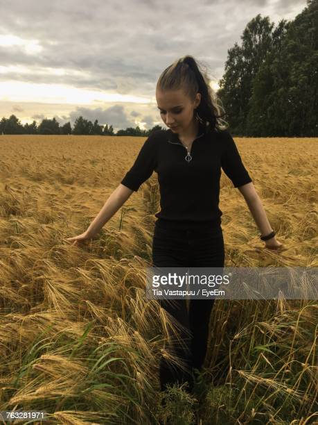 Beautiful Woman Touching Crops While Standing On Field Against Sky During Sunset