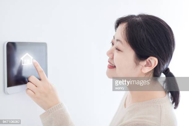 Beautiful woman touching tablet in smart home