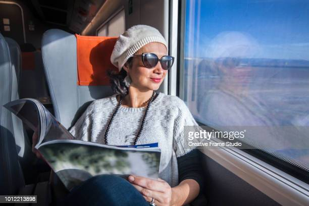 beautiful woman traveling by train enjoying the view holding a magazine - nature magazine stock pictures, royalty-free photos & images