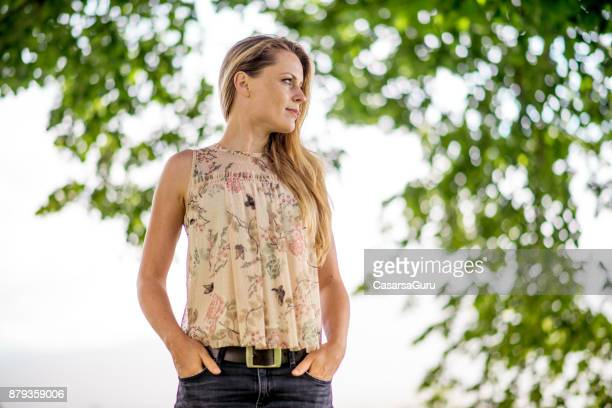 Beautiful Woman Under a Tree Looking Away with Hands in her Pockets