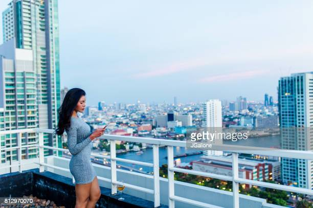 beautiful woman using a mobile phone on a rooftop at sunset overlooking the city - cocktail dress stock pictures, royalty-free photos & images