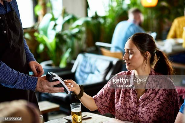 beautiful woman using contactless card payment for lunch bill - restaurant stock pictures, royalty-free photos & images