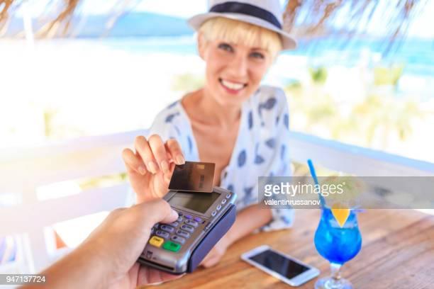 Hermosa mujer con tarjeta de crédito en la cafetería de la playa
