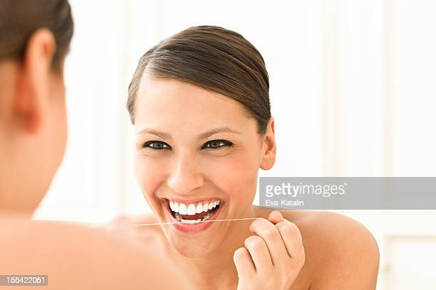 Beautiful woman using dental floss