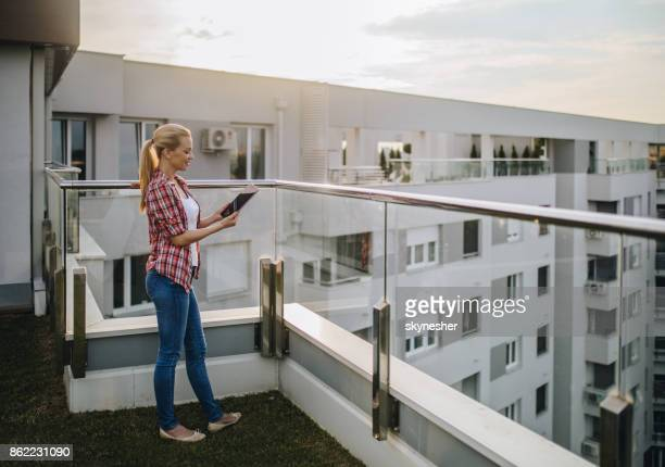beautiful woman using digital tablet on a penthouse balcony. - women of penthouse stock photos and pictures