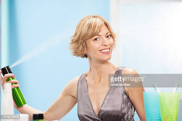 Beautiful woman using hair spray