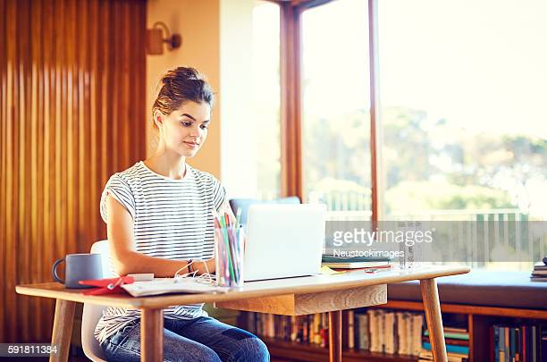 Beautiful woman using laptop at table by window