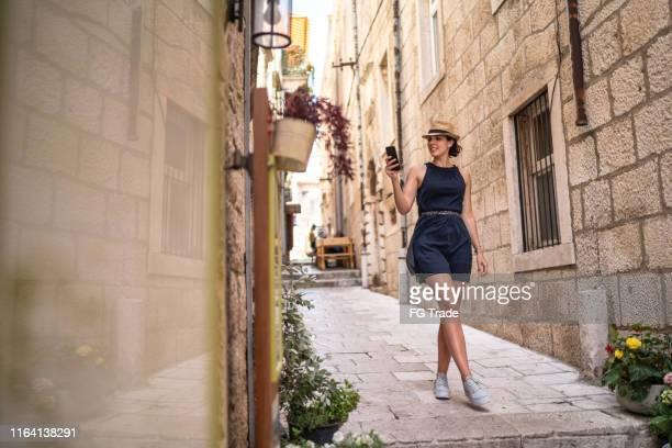beautiful woman using phone and walking in dubrovnik, croatia - dalmatia region croatia stock pictures, royalty-free photos & images