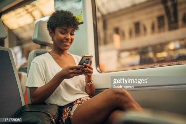 beautiful woman using phone in train - passenger train stock pictures, royalty-free photos & images