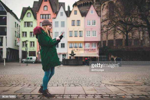 beautiful woman using phone outdoors in cologne on a winter day - cologne stock pictures, royalty-free photos & images