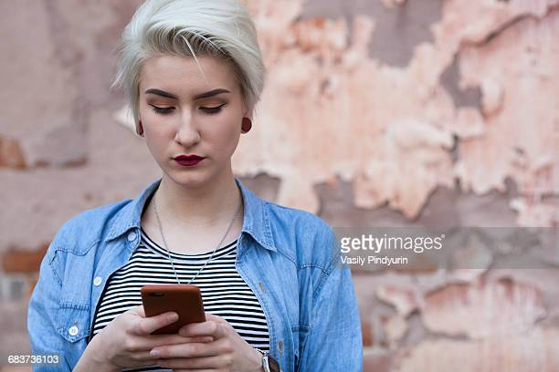 Beautiful woman using phone while standing against old wall