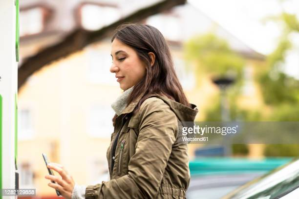 beautiful woman using smart phone for renting electric car at charging station - sharing economy stock pictures, royalty-free photos & images