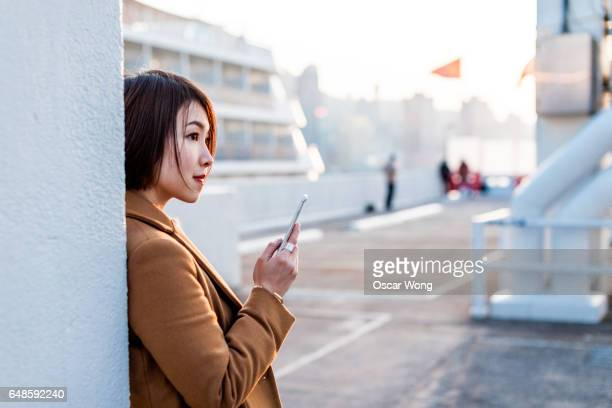 Beautiful woman using smartphone at outdoor car park