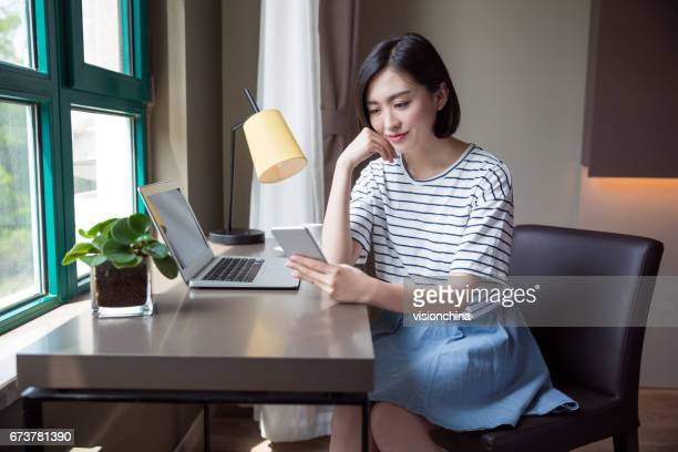 beautiful woman using smartphone with a laptop on desk at home