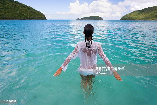 beautiful woman wading in serene water - waist deep in water stock pictures, royalty-free photos & images