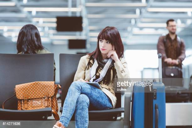 beautiful woman waiting for delayed flight in airport lounge - izusek stock pictures, royalty-free photos & images