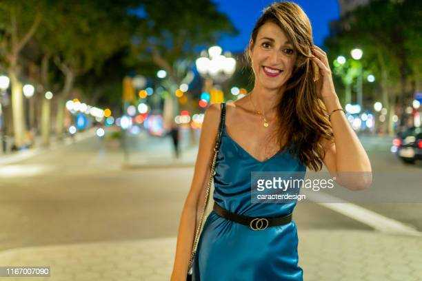 beautiful woman walking at dusk in passeig de gràcia, barcelona - satin dress stock pictures, royalty-free photos & images