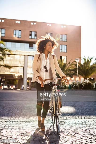 Beautiful woman walking holding her bicycle in the city