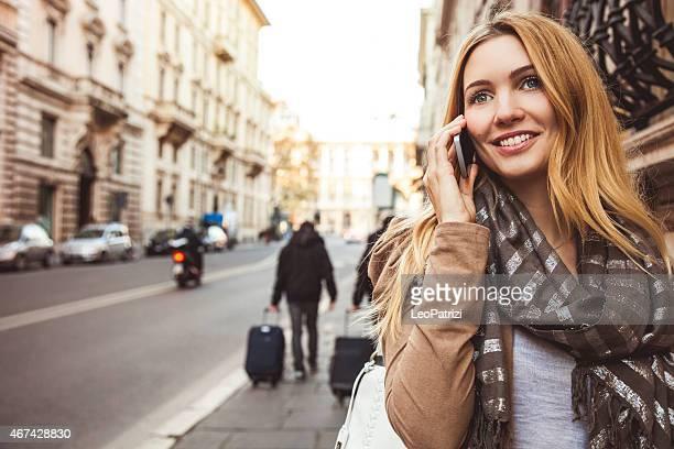 Schöne Frau zu Fuß in der Stadt reden auf mobile
