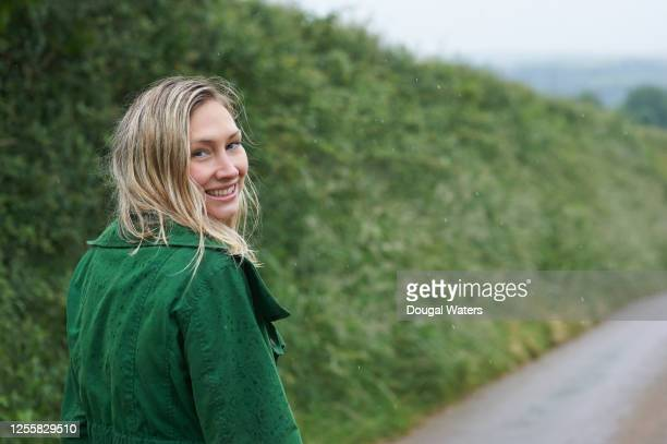 beautiful woman walking in the rain along small road in countryside. - solo adulti foto e immagini stock