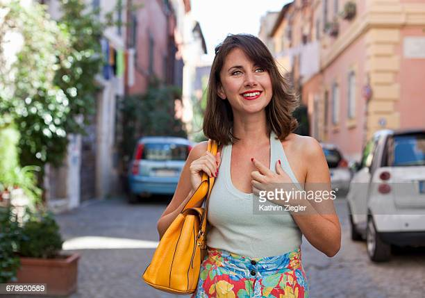 beautiful woman walking on cobblestone street - shoulder bag stock pictures, royalty-free photos & images
