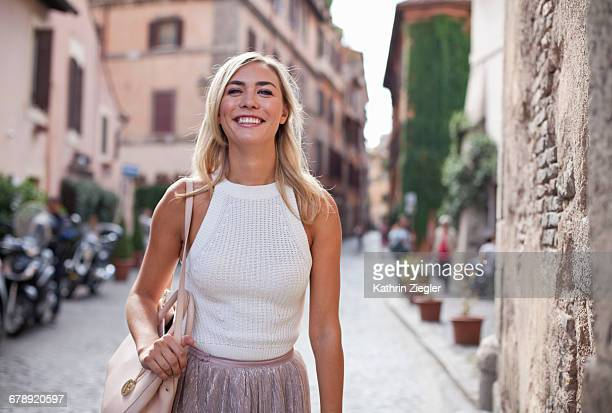 beautiful woman walking on cobblestone street - sleeveless top stock photos and pictures