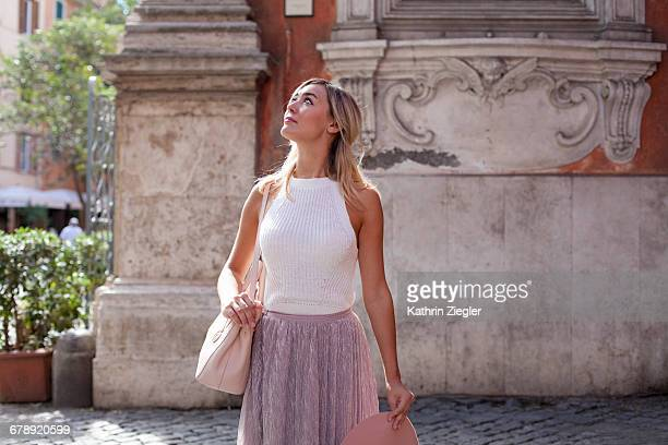 beautiful woman walking on cobblestone street - sleeveless stock pictures, royalty-free photos & images