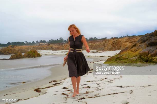 beautiful woman walking on shore at beach against sky - liga cerina stock pictures, royalty-free photos & images