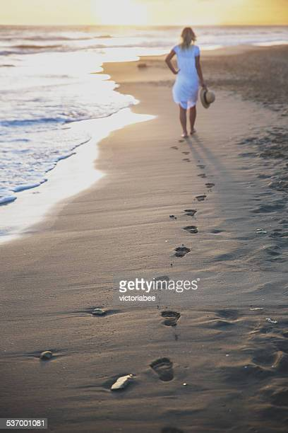Beautiful woman walking on the beach with her footprints back