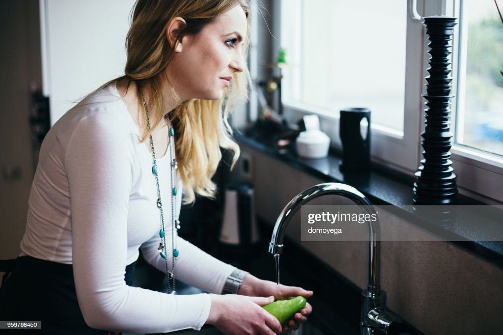 Beautiful woman washing vegetables in the kitchen : Stock Photo