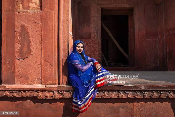 Beautiful woman wearing a colorful traditional Indian dress posing inside the Jama Masjid in old Delhi, India.