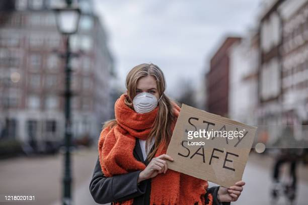 a beautiful woman wearing a face mask during virus outbreak - protestor mask stock pictures, royalty-free photos & images