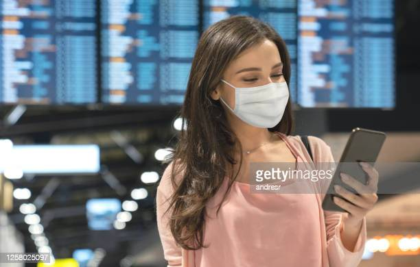 beautiful woman wearing a facemask at the airport while texting - biosecurity stock pictures, royalty-free photos & images