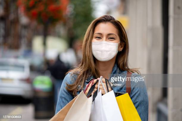 beautiful woman wearing a facemask while having fun shopping - state of emergency stock pictures, royalty-free photos & images