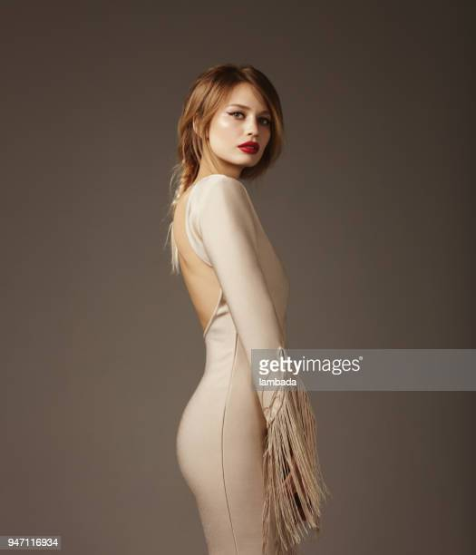 beautiful woman wearing beige bodycon dress - fringe dress stock photos and pictures