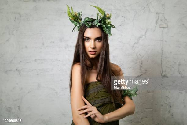 Beautiful woman wearing crown made from plant and green dress