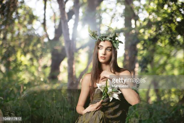 beautiful woman wearing crown made from plant at forest - fairy stock photos and pictures