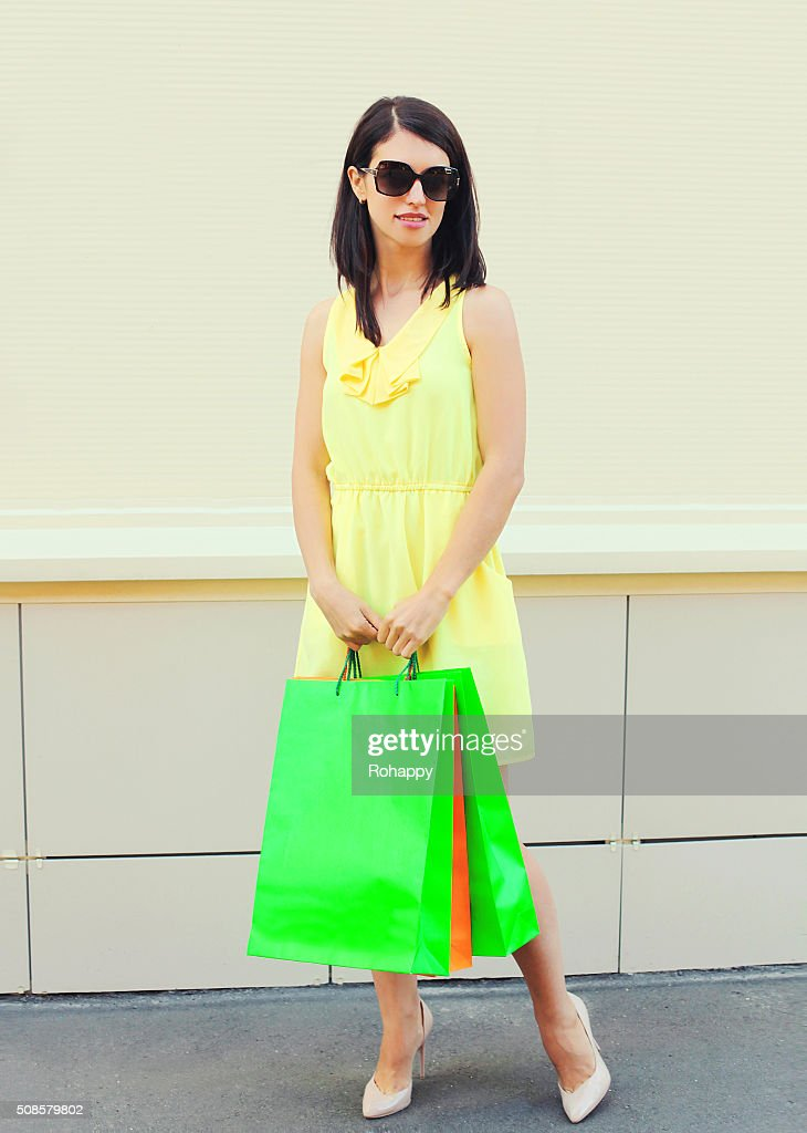 Beautiful woman wearing dress with shopping bags in city : Stock Photo