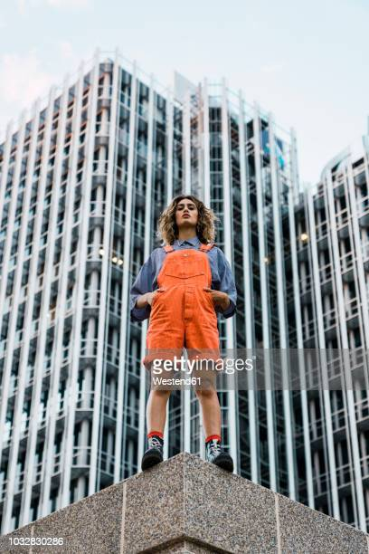 Beautiful woman wearing dungarees, standing on ledge in front of modern high-rise building