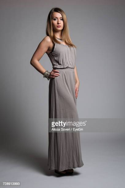 beautiful woman wearing gray gown standing with hand on hip against gray background - vestido de noite - fotografias e filmes do acervo