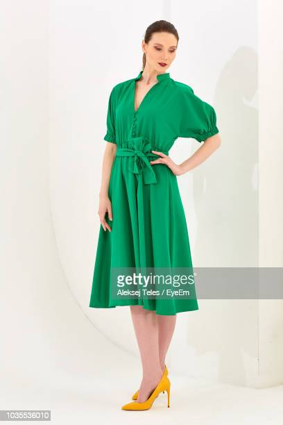 beautiful woman wearing green dress while standing over white background - cut out dress stock pictures, royalty-free photos & images