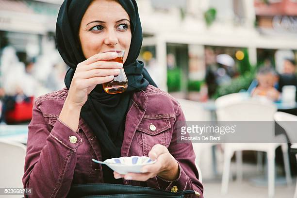 Beautiful Woman Wearing Headscarf Drinking Turkish Tea In A Cafè