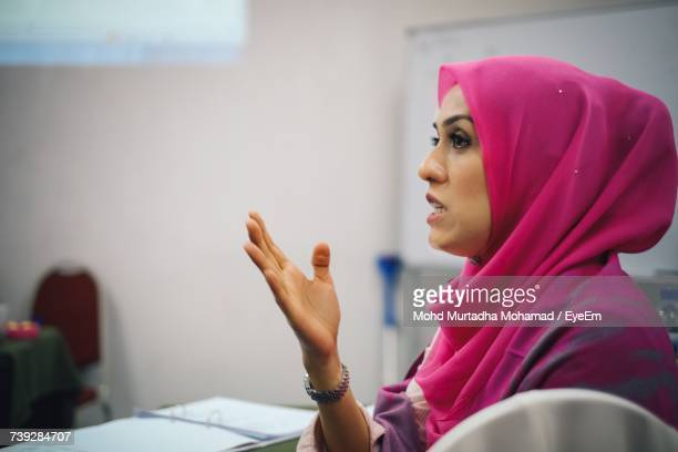 Beautiful Woman Wearing Hijab Gesturing While Sitting At Table In Office