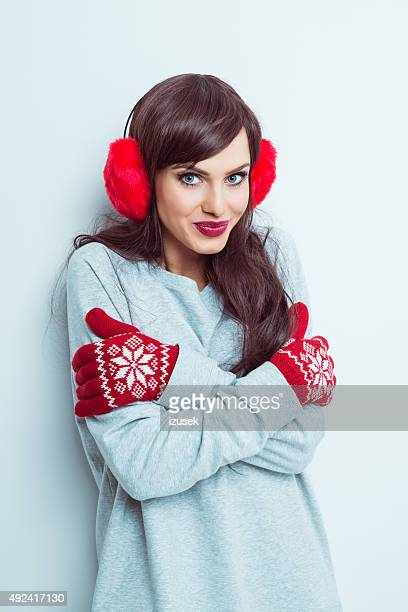 Beautiful woman wearing red earmuffs and gloves